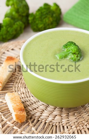 Traditional broccoli green cream vegan soup recipe with croutons on vintage background