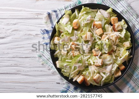 Traditional Caesar salad with croutons and parmesan on a plate. horizontal top view  - stock photo