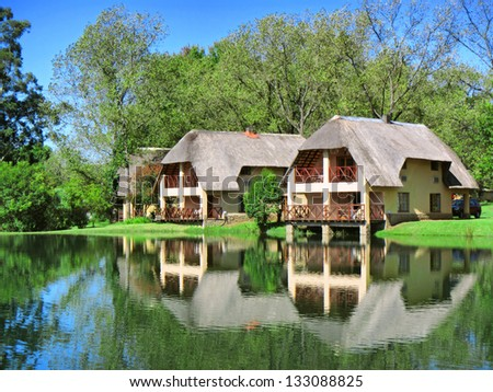 Traditional Cape Dutch house next to lake. Shot in Monks Cowl area, Drakensberg Mountains, South Africa. - stock photo
