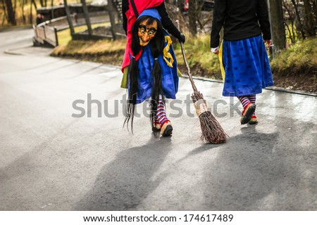 Traditional carnival in South Germany - Swabian-Alemannic Fastnacht. Two witches walking down the street. Selective focus on broom.  - stock photo