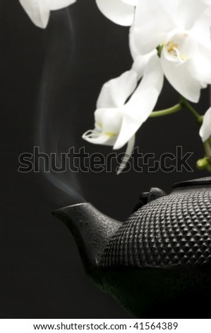 Traditional Cast Iron Oriental Tea Pot with vapour rising from spout & white Orchids in background - stock photo