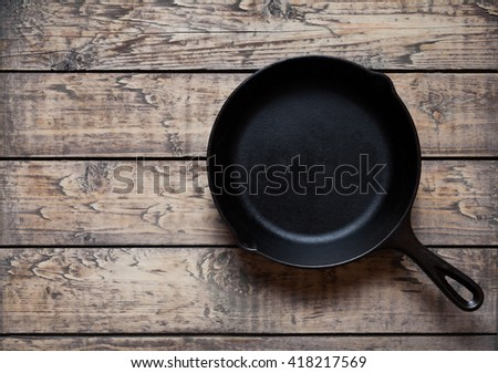Traditional cast iron skillet pan on vintage wooden table background. Kitchen equipment - stock photo