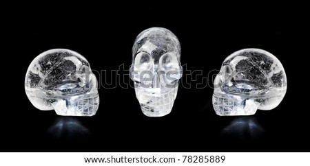 Traditional Central American quartz crystal carved skulls, isolated on black.