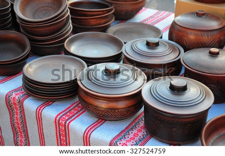 Traditional Ceramic Jugs on Decorative Towel. Showcase of Handmade Ceramic Pottery in a Roadside Market with Ceramic Pots and Clay Plates  - stock photo