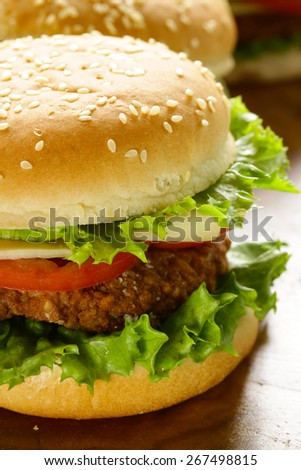 traditional cheeseburger with green lettuce and tomatoes - stock photo