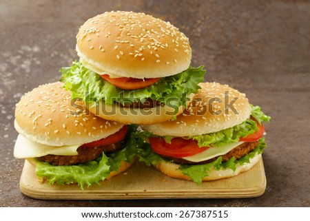 traditional cheeseburger with green lettuce and tomatoes on a wooden background - stock photo