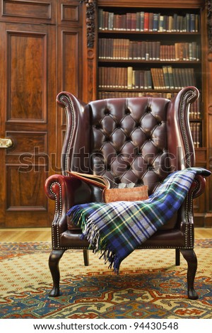 Traditional Chesterfield armchair with tartan blanket in classical library room - stock photo