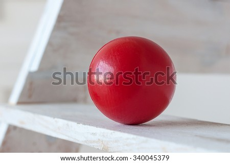 Traditional children's games. Air-filled, elastic red ball, decorative, on white wooden stairs. With empty space for text. - stock photo