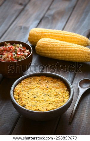 Traditional Chilean corn pie called Pastel de Choclo served with Pebre sauce and corn cobs in the back, photographed on dark wood with natural light (Selective Focus, Focus in the middle of the dish) - stock photo
