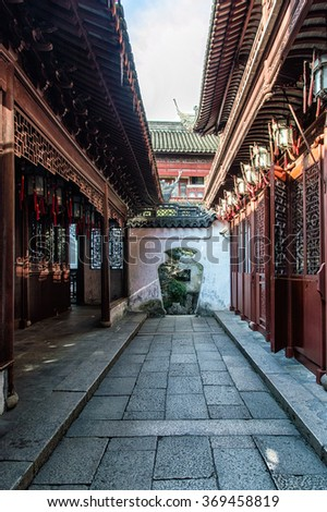Traditional Chinese architecture of red wooden screens, lanterns and pagoda tile roofs in the tranquil retreat of Yuyuan Gardens in the heart of Shanghai, China. - stock photo