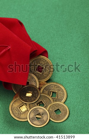 Traditional Chinese coins strewed out from a red purse on green cloth - stock photo