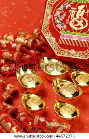 Traditional chinese firecrackers and gold ingots on the red. - stock photo