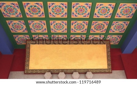 Traditional chinese flowery ceiling decoration,along with golden panel framed by geometrical motifs, in the Huating-Pavilion of Splendor buddhist temple, Kunming, Yunnan, China. - stock photo