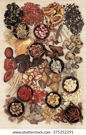 Traditional chinese herbal medicine in wooden bowls and loose over bamboo background. - stock photo