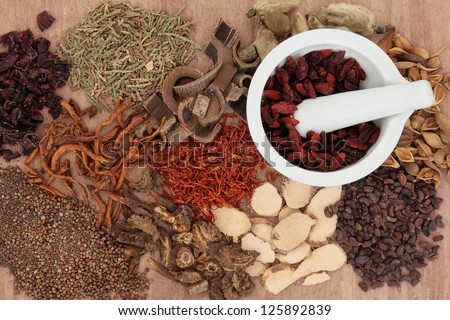 Traditional chinese herbal medicine selection with mortar and pestle over papyrus background. - stock photo