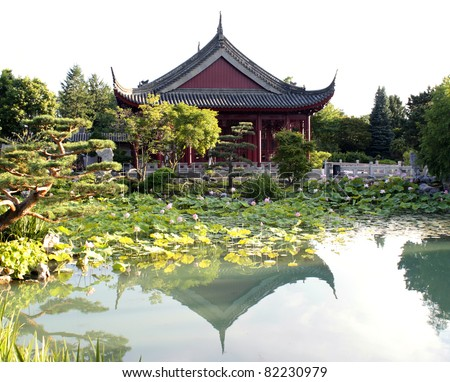 Traditional Chinese house near the pond with lotuses. Chinese temple, garden