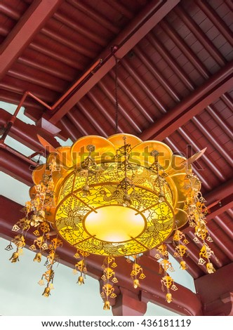 Traditional Chinese lantern is hanging on the roof of temple. - stock photo