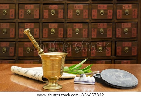 Traditional Chinese medicine shop (manual focus on the brass mortar) - stock photo