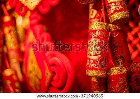 Traditional Chinese new year decorations. Chinese red firecrackers with the symbol of money. Red background. - stock photo