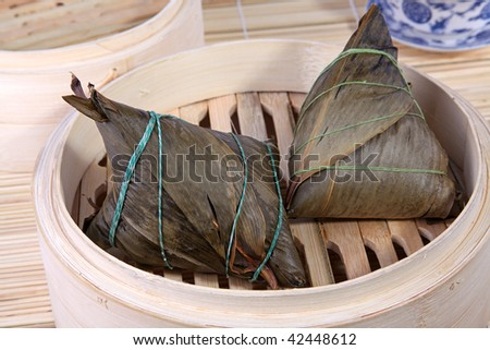 Traditional Chinese rice dumplings (Zongzi or Zong) over bamboo basket. Chinese ZongZi or Zong is traditionally eaten during Dragon Boat Festival (DuanWu festival). - stock photo