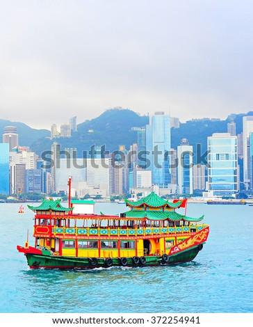 Traditional chinese-style boat sailing in Hong Kong harbor  - stock photo