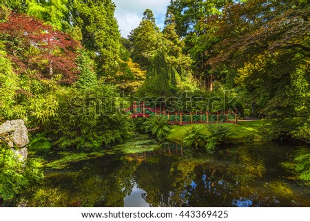 Traditional Chinese style garden with pond and ornate wooden red bridge. - stock photo