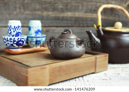 Traditional chinese tea ceremony accessories (tea pot and tea pair) on the tea table, selective focus - stock photo