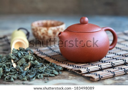 Traditional chinese tea ceremony accessories: tea pot, cup and green tea on the wooden table, selective focus - stock photo