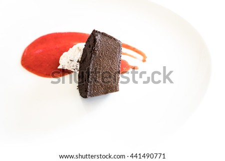Traditional chocolate cake with ice cream and sorbet sauce isolated on white background - stock photo