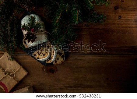 Traditional Christmas Baking: Stollen with dried fruits and nuts, sprinkled with powdered sugar. Miniature Christmas cake. Against Christmas tree branches, cones and gifts Top view copy space