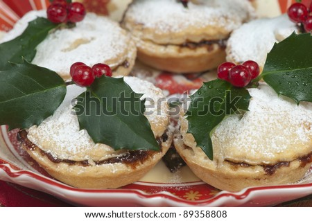 Traditional Christmas English mince pies decorated with icing sugar and holly with berries.  On an attractive  old fashioned cream and red plate. - stock photo