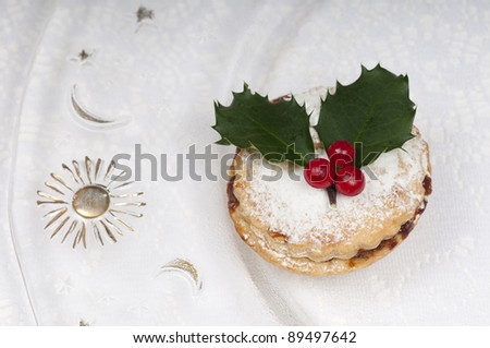 Traditional Christmas English mincepies decorated with icing sugar and holly with berries.  On an attractive glass plate with sun and moon. - stock photo