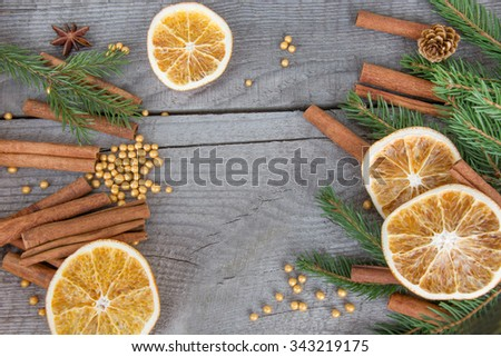 Traditional Christmas frame with spices, decorated with dried orange around central copyspace on a rustic wood background for your Christmas message.  - stock photo