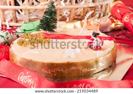 Traditional Christmas fruit cake with hamper basket at the background  - stock photo