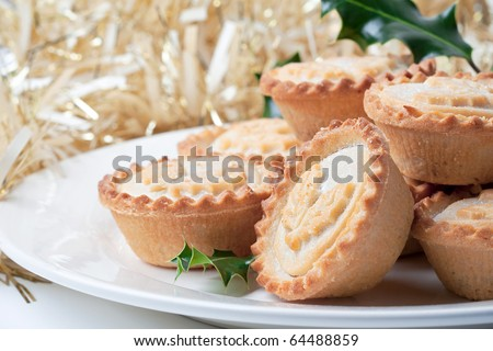 Traditional christmas mince pies on tinsel decorated table - stock photo