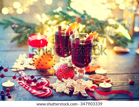 Traditional Christmas Mulled Wine hot drink with cinnamon stick, slices of orange and spices, on holiday decorated Christmas table. Christmas dinner