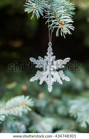 Traditional Christmas or new year decorated tree with a silver snowflake toy - stock photo