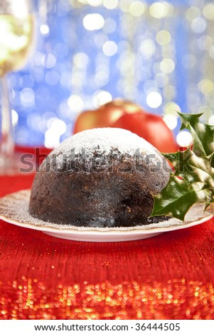 traditional christmas pudding with decorations on red glitter, shallow DOF - stock photo