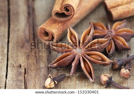 Traditional Christmas spices - star anise, cloves and cinnamon bark sticks - on a rustic wooden table - stock photo
