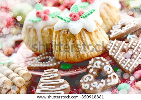 Traditional Christmas sweets: cookies, cakes, cupcakes, candy. Toning and bokeh effect. - stock photo