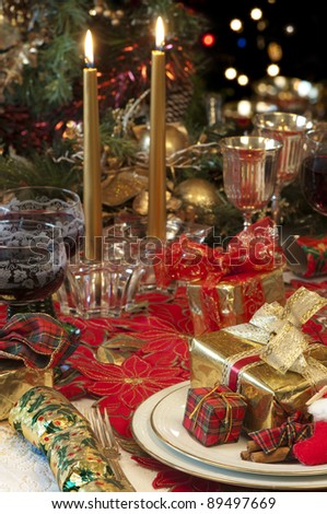 Traditional Christmas table setting with tree, presents, candles, lights, cracker, and red wine,
