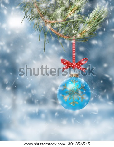 Traditional Christmas Tree Decoration hanging from a tree branch with a snow scene background. - stock photo