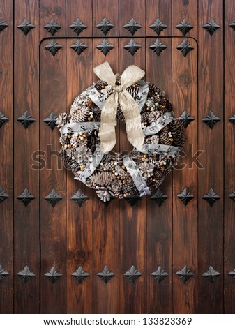 Traditional Christmas wreath in silver and gold on wooden door - stock photo