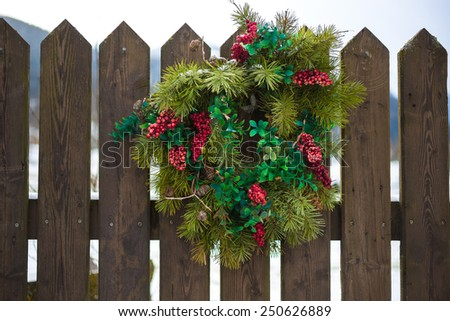 Traditional Christmas wreath with red berries hanging on wooden fence - stock photo