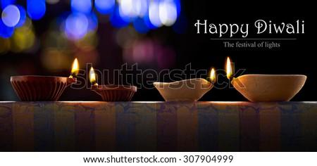Traditional clay diya lamps lit during diwali celebration - stock photo
