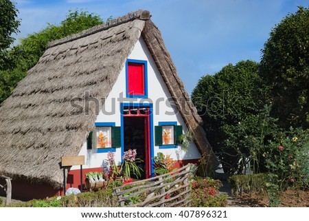 Traditional colored houses at Santana village, Madeira Island. Typical triangular houses with straw roof, red door and small windows with shutters, originally built by local farmers. - stock photo
