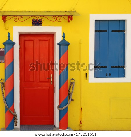 traditional colorful doorway to the home in Burano village, borgo on venetian lagoon famous for vivid painted houses, Venice - stock photo