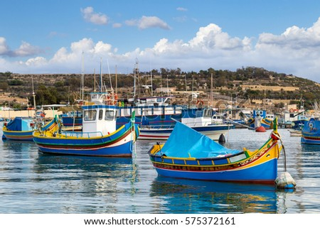 Traditional colourful painted Maltese fishing boats, called luzzu, in the small fishing village Marsaxlokk on Malta.