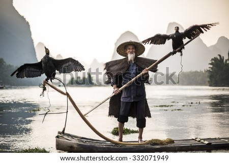 traditional cormorant fisherman showing of his birds on Li river near Xingping, Guangxi province, China. - stock photo