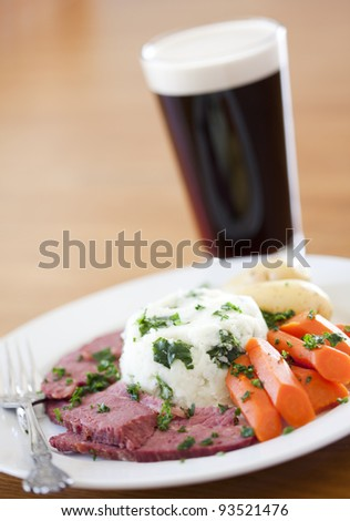 Traditional Corned Beef Dinner with Beer on a table - stock photo
